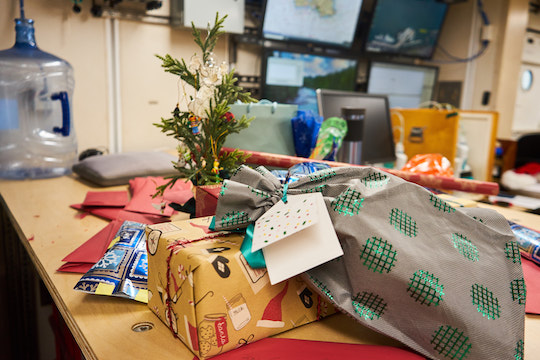 A small pile of wrapped Christmas presents and red envelopes sit under a tiny, decorated Christmas tree. In the background, several computer monitors display oceanographic data.