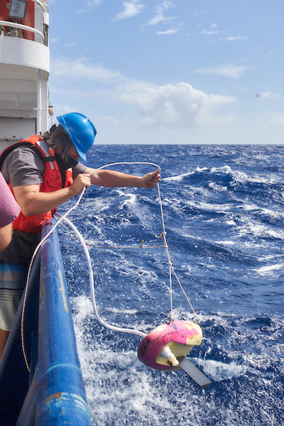 A man in a gray t-shirt, orange life vest, and blue hard hat is leaning over the side of a blue ship. He's holding a white rope tied to a pink-and-yellow plastic sled with a black rudder underneath. Plastic tubing is running from the sled back to the ship.