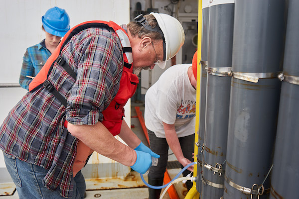 A man with a goatee and glasses is bent over, holding a tube connected to a gray plastic bottle. He is wearing a white hardhat, orange life vest, and blue nitrile gloves in addition to a plaid shirt and jeans. Behind him are two women, also wearing hardhats.