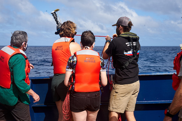 Four people are facing the ocean with their backs to the camera. Three of them have orange life vests on; one has a black shirt and khaki shorts. Two people are holding red ropes while a third is holding a black cylinder with sensors attached to the top.