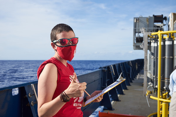 A person with a buzz cut and holding a clipboard is giving a thumbs-up signal to the camera. Their sunglass lenses, mask, and t-shirt are all bright red. In the background and out of focus is a blue barrier and, beyond that, the ocean. To the right of the photo is a yellow metal frame surrounded by gray plastic bottles, also out of focus.