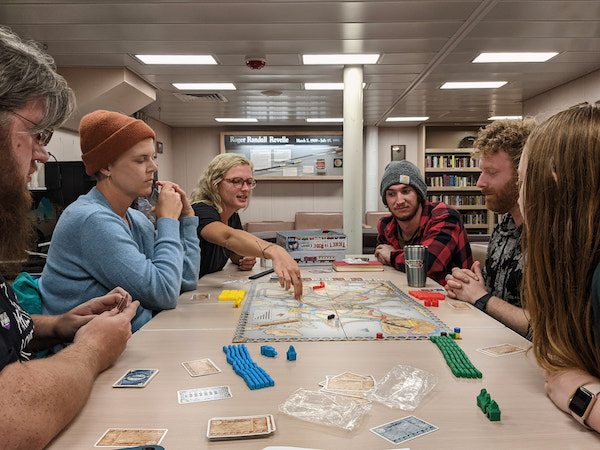 Six people are gathered around a table playing a board game. The board is in the middle and each person has an array of plastic pieces and cards in front of them.