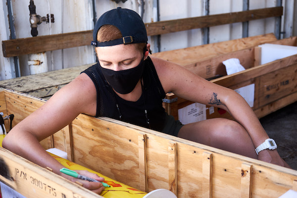 A woman is sitting next to a plywood box containing a yellow cylindrical piece of equipment. She is wearing a backwards baseball hat over short-cropped hair, a dark mask, and a black tank top. She's reaching into the box and drawing on the equipment with a sharpie; in the background is more plywood.