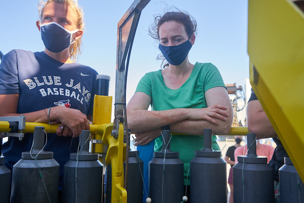 Two women are pictured. One is wearing a navy Toronto Blue Jays t-shirt, the other is wearing a light green t-shirt; both have navy blue masks on. In front of them are several large, dark gray, plastic bottles attached to a yellow metal frame.