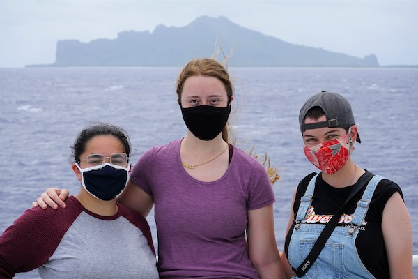 Three women are standing in front of the ocean. One is dressed in a gray and maroon baseball t-shirt, one in a purple t-shirt, and the third in a black t-shirt, overalls, and a backwards baseball hat. All three women are wearing masks. In the distance, silhouetted against the sky, is the island of Maupiti, French Polynesia.
