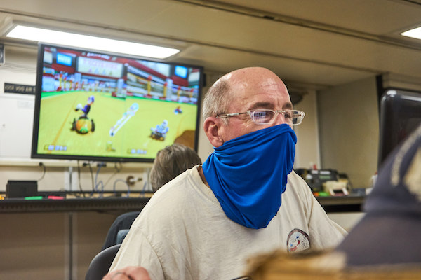 The camera is focused on a man with clear-rimmed glasses, a white t-shirt, and a blue neck gaiter. He is staring intently at a computer screen. Behind him, a large flat-screen TV is mounted on the wall. The image on the TV is a split screen view of two Mario Kart players.