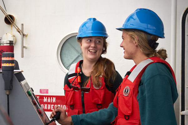 Two women in blue hard hats and orange life vests are smiling at each other. The one on the right is holding a joystick.