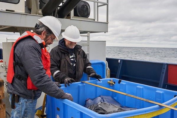 Two men in white hardhats and dark coats are standing in front of a large blue plastic tub sitting on the deck of a ship. In the background you can see the ocean and a cloudy sky.