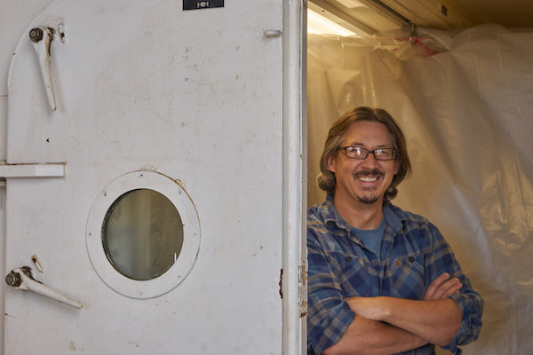 A man with chin-length dark hair, a goatee, and glasses is leaning up on a door frame. He's wearing a blue plaid shirt and behind him is a wall of plastic sheeting.