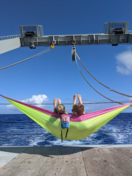 Two people are sitting in a green and pink hammock at the back of a ship. In front of them, the sky and the ocean are both bright blue.