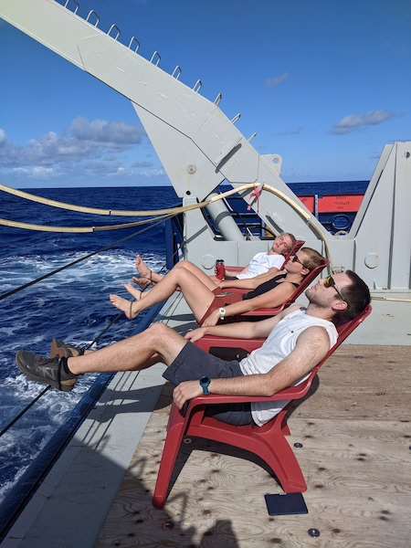 At the back of a ship, three people are reclining in red Adirondack chairs. All three appear to be sleeping.