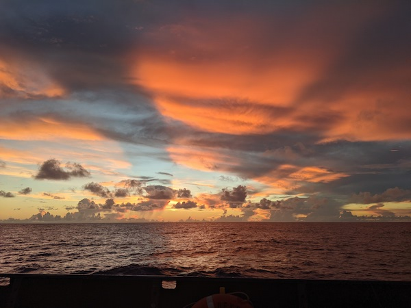 A picture of a gorgeous sunset over the ocean. The sky, while cloudy, is blue and yellow, and the clouds are lit up a pink-orange color.