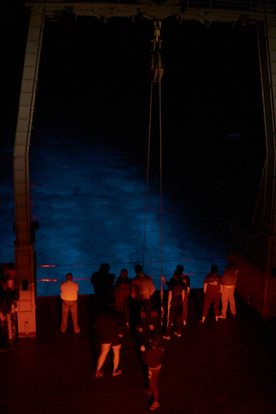 A crowd of people is standing at the back of a ship, bathed in red light. Behind them, the wake of the ship is glowing blue with bioluminescence.