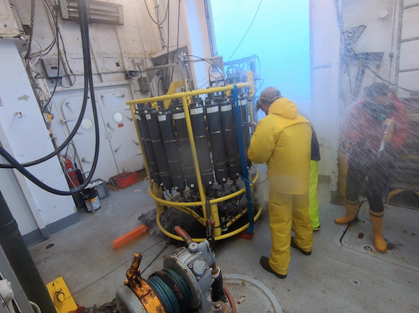 The CTD, a yellow metal frame with large gray plastic bottles attached, is in the middle of a big room. Two men (one mostly obscured by the other) are in rain gear, standing close to the frame. A person in red is to the right of the frame and is getting doused by a big wave.
