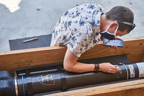 A person with a buzzed hair and a white-and-blue Hawaiian print shirt is drawing on a black metal cylinder contained within a plywood box.