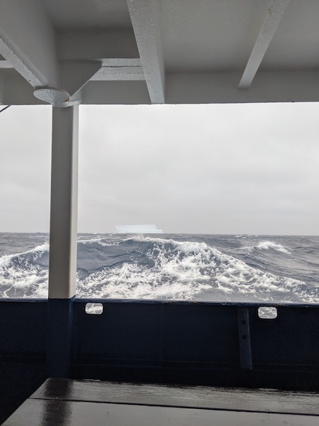 A large, blueish tabular iceberg arises from the horizon of a stormy grey ocean.