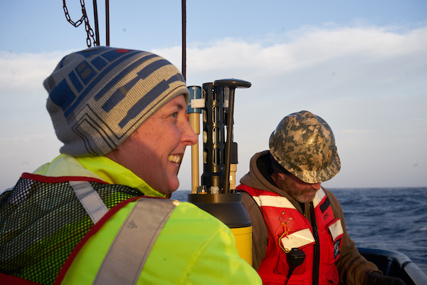 Two people are standing at the back of the boat with a calm ocean behind them. Both are wearing high-visibility work gear; one has on an R2-D2 beanie while the other is sporting a camouflage hard hat.